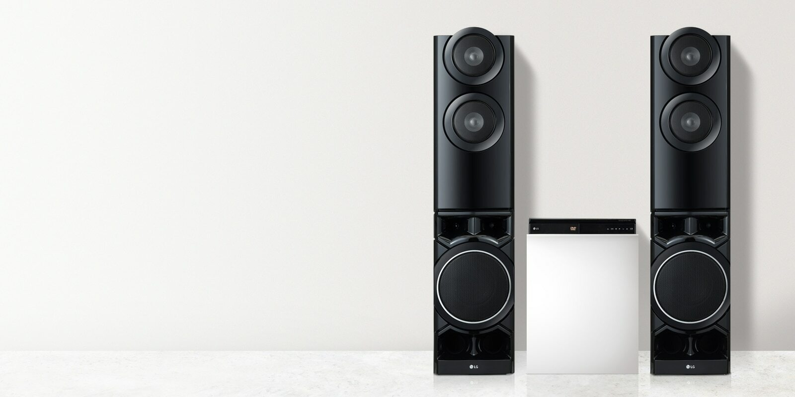 Two tower speakers and a DVD player on the platform are in the white living room.
