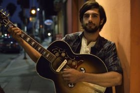 Picture shows a guitarist outdoors at night illuminated only by the ambient light.