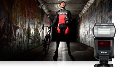 D500 photo of a mountain biker in low light standing next to his bike, inset with the SB-5000 Speedlight