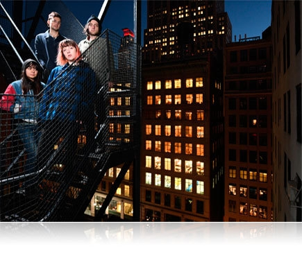 D500 photo of four people on a fire escape with a city night scene in the background