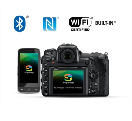 Photo of the rear of the D500 and a smartphone with the SnapBridge app logo on the LCD of both, along with the Wi-Fi, NFC and Bluetooth logos