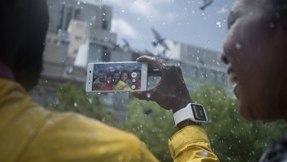 Person using the Xperia Z3+ to take a selfie in the rain