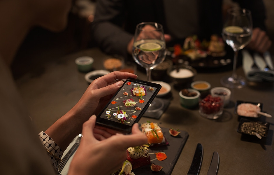 Someone using the Xperia Z3+ to take pictures of food in a dimly lit restaurant