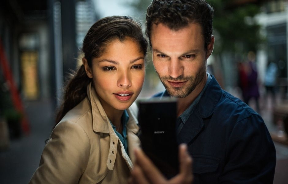 Couple on a city street at night, consulting their Xperia Z3+